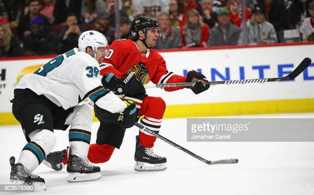 Brandon Saad of the Chicago Blackhawks fires a shot past Logan Couture of the San Jose Sharks at the United Center on February 23 2018 in Chicago...