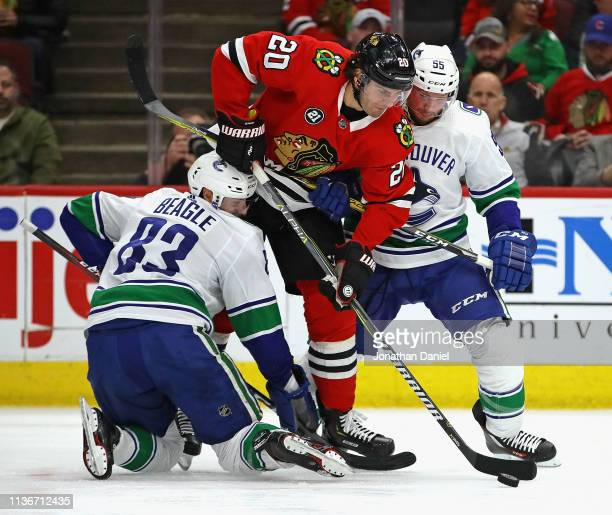 Brandon Saad of the Chicago Blackhawks forces his way between Jay Beagle and Alex Biega of the Vancouver Canucks at the United Center on March 18...