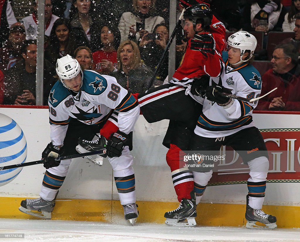 Brandon Saad #20 of the Chicago Blackhawks gets caught between Brent Burns #88 and Tim Kennedy #46 of the San Jose Sharks at the United Center on February 15, 2013 in Chicago, Illinois.
