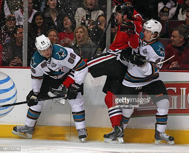Brandon Saad of the Chicago Blackhawks gets caught between Brent Burns and Tim Kennedy of the San Jose Sharks at the United Center on February 15...