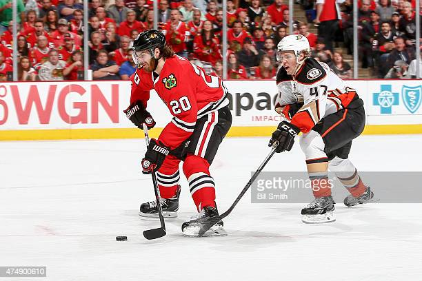 Brandon Saad of the Chicago Blackhawks handles the puck ahead of Hampus Lindholm of the Anaheim Ducks, resulting in a goal in the second period, in...