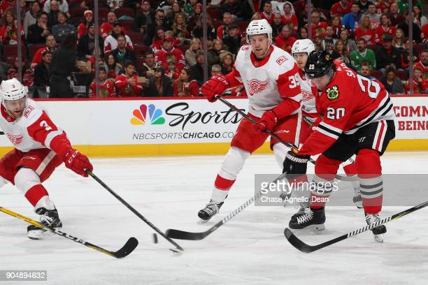 Brandon Saad of the Chicago Blackhawks hits the puck against Nick Jensen of the Detroit Red Wings as Anthony Mantha watches from behind in the second...