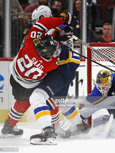 Brandon Saad of the Chicago Blackhawks is hit by Colton Parayko of the St. Louis Blues after taking a shot against Jake Allen at the United Center on...
