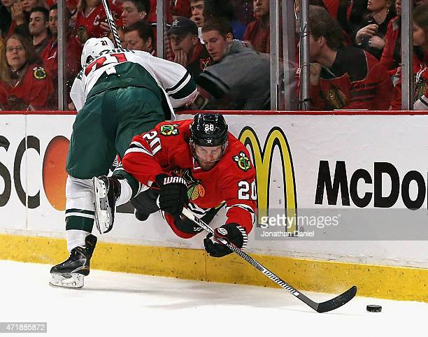 Brandon Saad of the Chicago Blackhawks is sent into air by Kyle Brodziak of the Minnesota Wild as he tries to get to the puck in Game One of the...