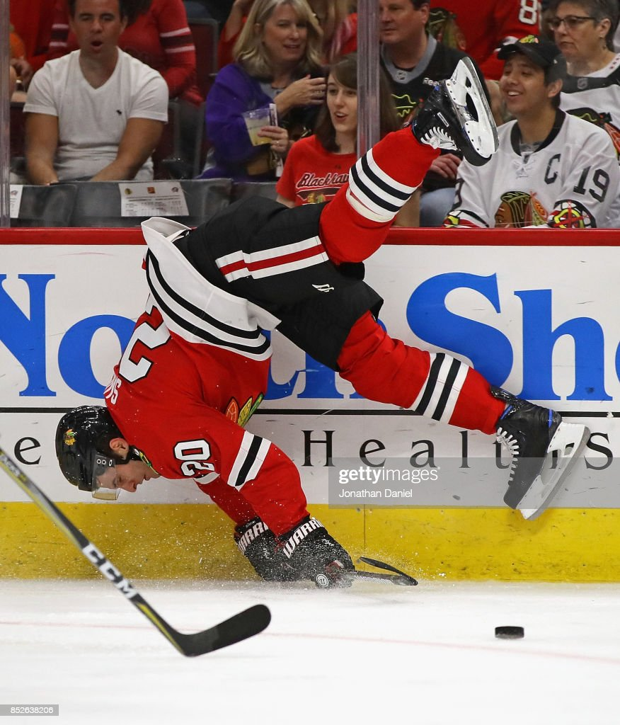 Brandon Saad #20 of the Chicago Blackhawks is upended by Jacob Graves the Columbus Blue Jackets during a preseason game at the United Center on September 23, 2017 in Chicago, Illinois.