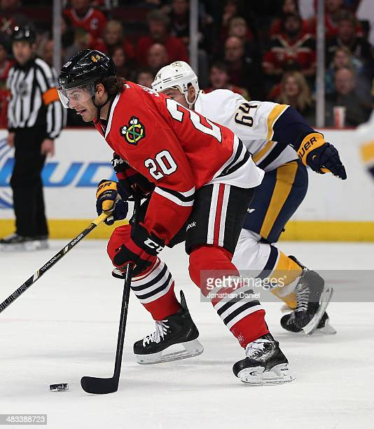 Brandon Saad of the Chicago Blackhawks moves past Victor Bartley of the Nashville Predators at the United Center on March 23 2014 in Chicago Illinois...