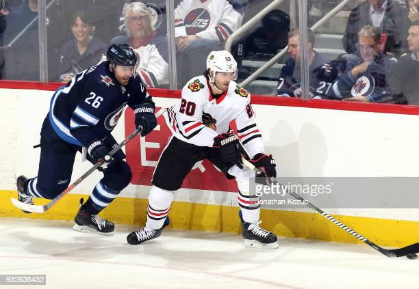 Brandon Saad of the Chicago Blackhawks plays the puck along the boards away from Blake Wheeler of the Winnipeg Jets during third period action at the...