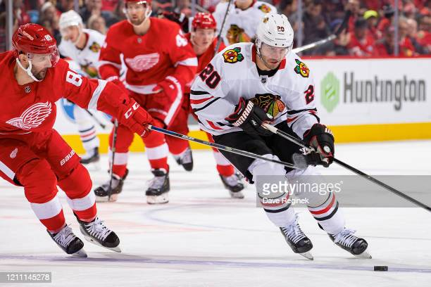 Brandon Saad of the Chicago Blackhawks protects the puck from Sam Gagner of the Detroit Red Wings during an NHL game at Little Caesars Arena on March...