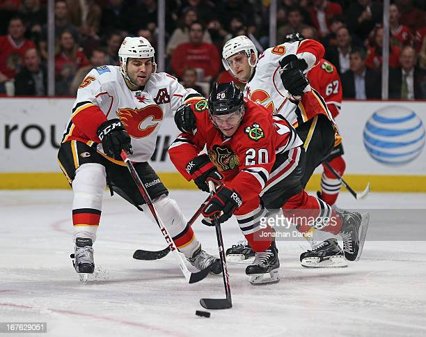 Brandon Saad of the Chicago Blackhawks tries to control the puck under pressure from Mark Giordano of the Calgary Flames at the United Center on...