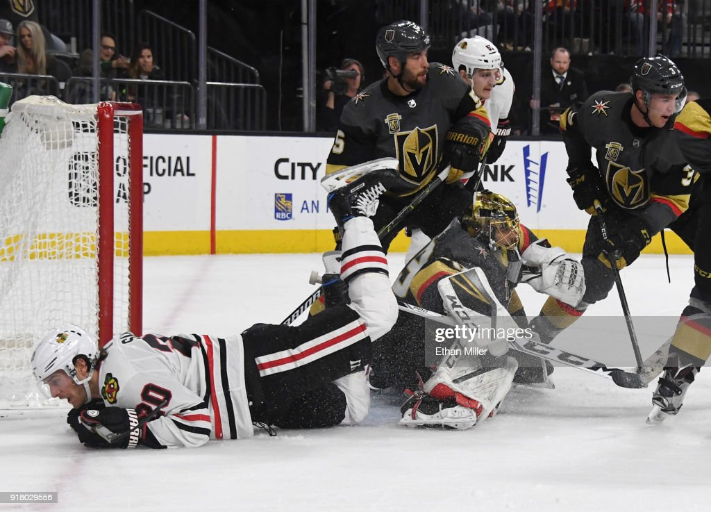 Brandon Saad #20 of the Chicago Blackhawks trips over Marc-Andre Fleury #29 of the Vegas Golden Knights who defends the net with teammates Deryk Engelland #5 and Brayden McNabb #3 in the third period of their game at T-Mobile Arena on February 13, 2018 in Las Vegas, Nevada. The Golden Knights won 5-2.