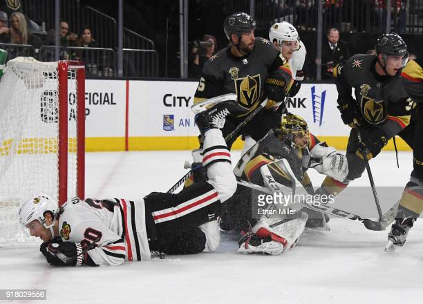 Brandon Saad of the Chicago Blackhawks trips over MarcAndre Fleury of the Vegas Golden Knights who defends the net with teammates Deryk Engelland and...