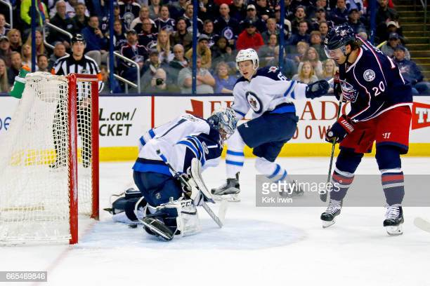 Brandon Saad of the Columbus Blue Jackets slides the puck through the legs of Eric Comrie of the Winnipeg Jets for a goal during the second period on...