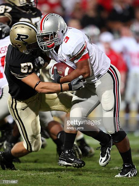 Brandon Saine of the Ohio State Buckeyes runs with the ball while defended by Tyler Haston the Purdue Boilermakers during the game on October 6, 2007...