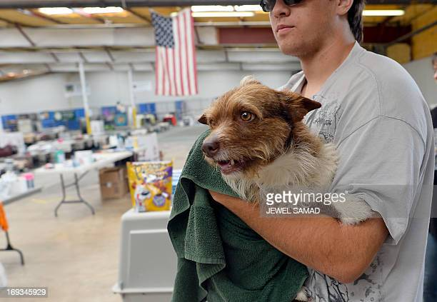 Brandon Sarrels brings a dog that his mother found in the rubble of a tornado devastated house to a pet shelter on May 23 2013 in Moore Oklahoma...