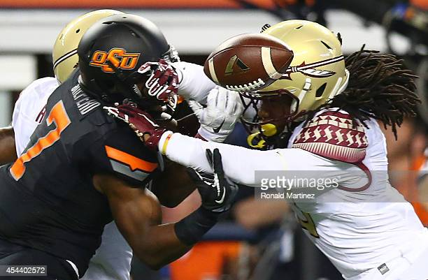 Brandon Sheperd of the Oklahoma State Cowboys tries to make the catch as he is defended by Tyler Hunter and Ronald Darby of the Florida State...