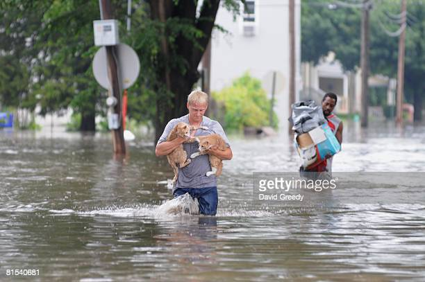 Brandon Smith carries his two cats Fry and Bender to dry land from their flooded and evacuated home on June 12 2008 in Cedar Rapids Iowa Much of the...