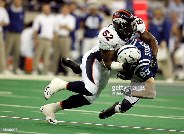 Brandon Stokley of the Indianapolis Colts is tackled by D.J. Williams of the Denver Broncos in the second quarter during the AFC Wildcard playoff...