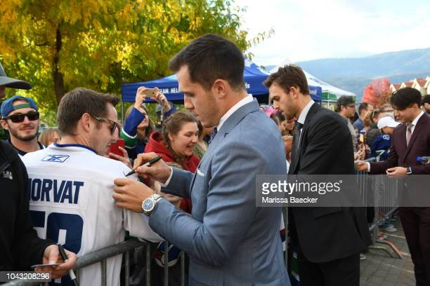 Brandon Sutter and Bo Horvat of the Vancouver Canucks sign autographs prior to the final preseason game against the Arizona Coyotes at Prospera Place...