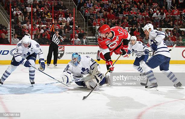 Brandon Sutter of the Carolina Hurricanes goes airbourne as he backhands the puck to score a goal past the defense of Dion Phaneuf of the Toronto...