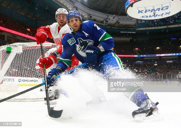 Brandon Sutter of the Vancouver Canucks and Andreas Athanasiou of the Detroit Red Wings look for loose puck during their NHL game at Rogers Arena...
