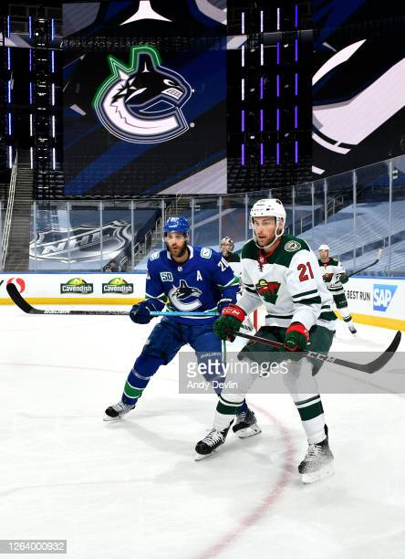 Brandon Sutter of the Vancouver Canucks and Carson Soucy of the Minnesota Wild watch the play during the second period of Game Two of the Western...