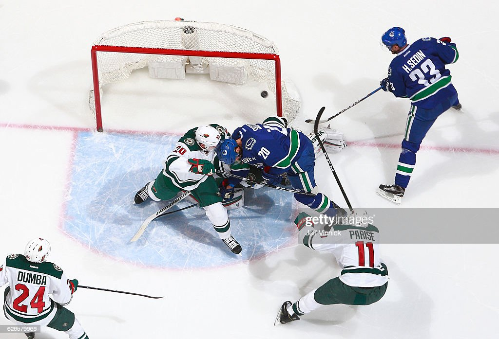 Brandon Sutter #20 of the Vancouver Canucks and Ryan Suter #20 of the Minnesota Wild collide with Darcy Kuemper #35 of the Minnesota Wild as Henrik Sedin #33 of the Vancouver Canucks watches the puck go into the net during their NHL game at Rogers Arena November 29, 2016 in Vancouver, British Columbia, Canada. The goal was disallowed because of goalie interference by Sutter. Vancouver won 5-4.