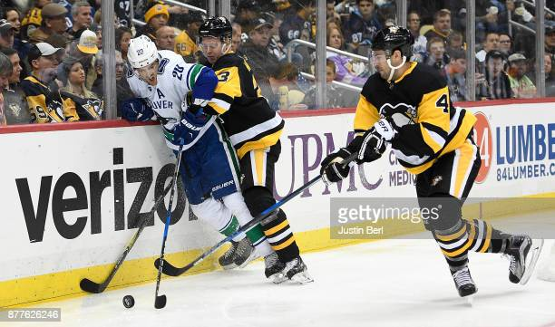 Brandon Sutter of the Vancouver Canucks battles for the puck along the boards with Olli Maatta of the Pittsburgh Penguins and Justin Schultz in the...