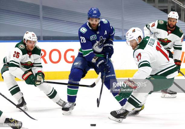Brandon Sutter of the Vancouver Canucks goes for the puck between Jonas Brodin and Marcus Foligno of the Minnesota Wild during the first period of...