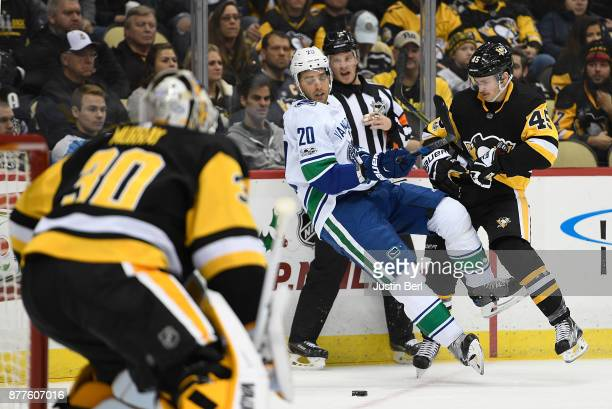 Brandon Sutter of the Vancouver Canucks is knocked to the ice by a check from Josh Archibald of the Pittsburgh Penguins in the first period during...
