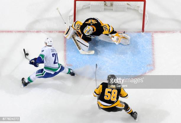 Brandon Sutter of the Vancouver Canucks moves the puck in front of Matt Murray and Kris Letang of the Pittsburgh Penguins at PPG Paints Arena on...