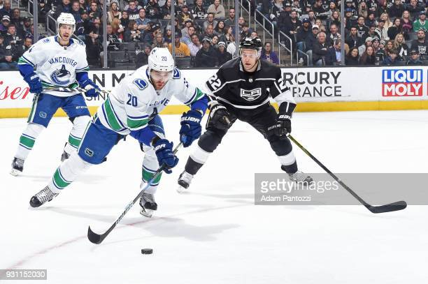 Brandon Sutter of the Vancouver Canucks skates after the puck against Trevor Lewis of the Los Angeles Kings at STAPLES Center on March 12 2018 in Los...