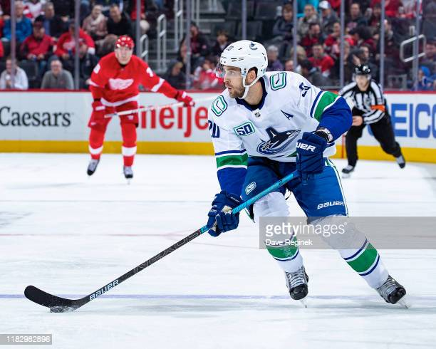 Brandon Sutter of the Vancouver Canucks skates up ice with the puck against the Detroit Red Wings during an NHL game at Little Caesars Arena on...