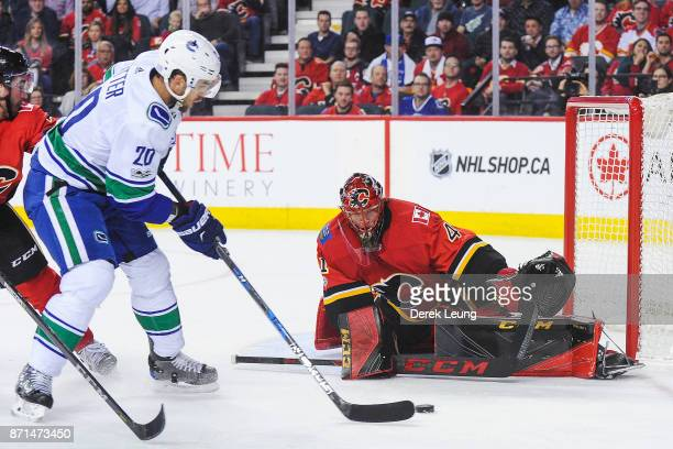 Brandon Sutter of the Vancouver Canucks takes a shot on Mike Smith of the Calgary Flames during an NHL game at Scotiabank Saddledome on November 11...