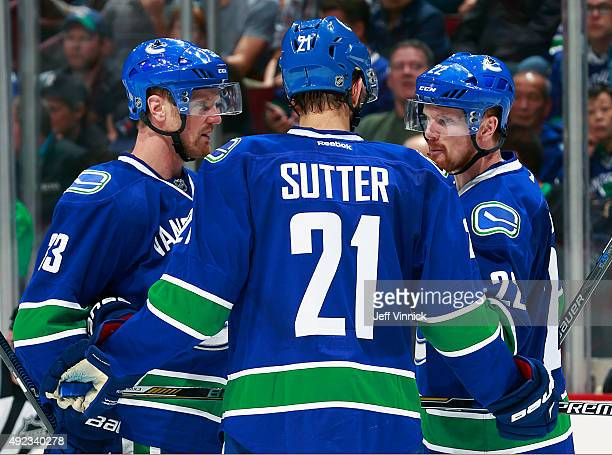 Brandon Sutter of the Vancouver Canucks talks to teammates Henrik Sedin and Daniel Sedin during their NHL game against the Calgary Flames at Rogers...