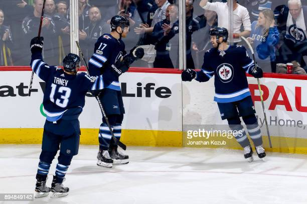 Brandon Tanev Adam Lowry and Josh Morrissey of the Winnipeg Jets celebrate a third period goal against the Vancouver Canucks at the Bell MTS Place on...