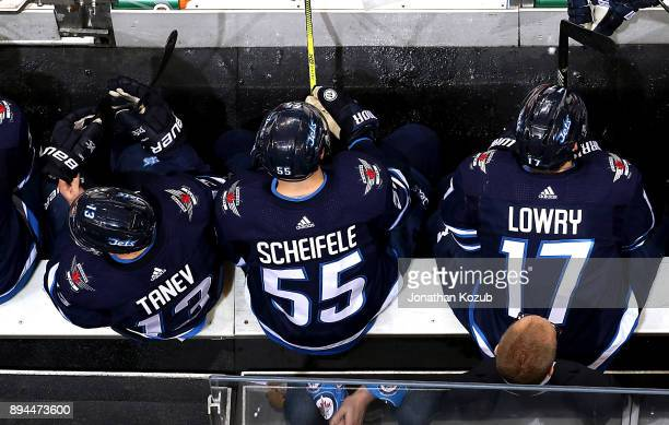 Brandon Tanev Mark Scheifele and Adam Lowry of the Winnipeg Jets keep an eye on the play from the bench during second period action against the St...