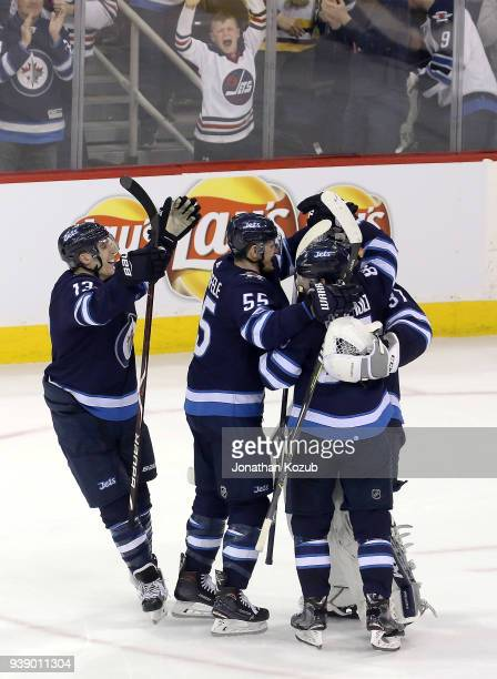 Brandon Tanev Mark Scheifele and Mathieu Perreault of the Winnipeg Jets embrace goaltender Connor Hellebuyck following a 54 shootout victory over the...