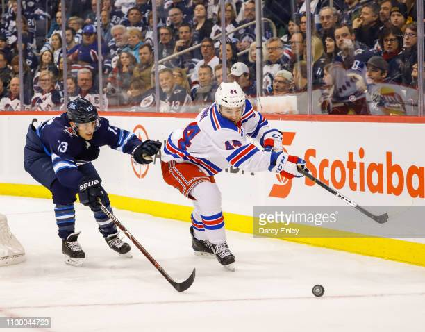 Brandon Tanev of the Winnipeg Jets and Neal Pionk of the New York Rangers chase the loose puck during first period action at the Bell MTS Place on...