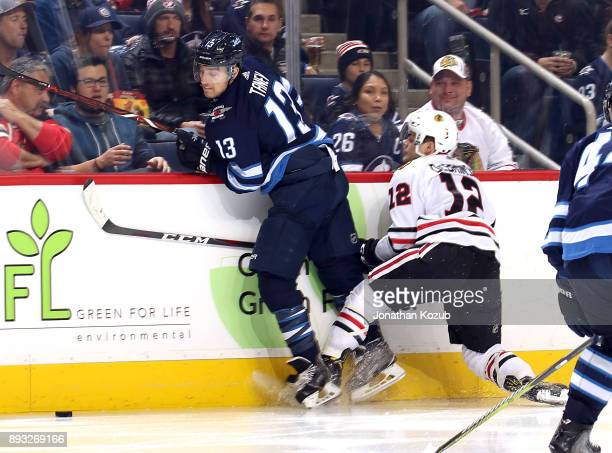 Brandon Tanev of the Winnipeg Jets avoids a check along the boards from Alex DeBrincat of the Chicago Blackhawks during third period action at the...
