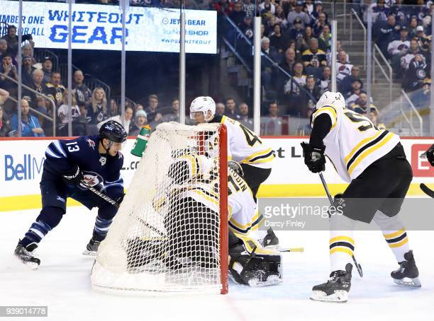 Brandon Tanev of the Winnipeg Jets banks the puck off goaltender Anton Khudobin of the Boston Bruins for a first period goal at the Bell MTS Place on...