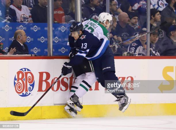 Brandon Tanev of the Winnipeg Jets checks Esa Lindell of the Dallas Stars into the boards during second period action at the Bell MTS Place on March...