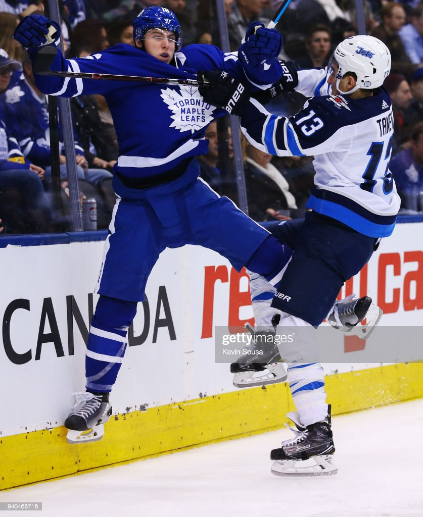 Brandon Tanev #13 of the Winnipeg Jets checks Mitch Marner #16 of the Toronto Maple Leafs during the third period at the Air Canada Centre on March 31, 2018 in Toronto, Ontario, Canada.