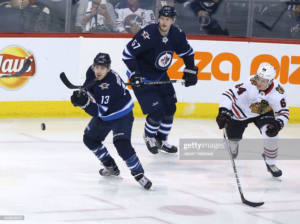 Brandon Tanev #13 of the Winnipeg Jets clears the puck in front of Tyler Myers #57 of the Winnipeg Jets and David Kampf #64 of the Chicago Blackhawks during NHL action on April 7, 2018 at Bell MTS Place in Winnipeg, Manitoba.