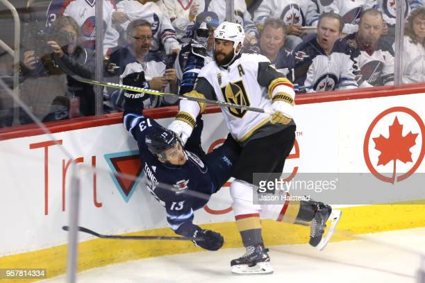 Brandon Tanev of the Winnipeg Jets is checked into the boards by Deryk Engelland of the Vegas Golden Knights during the first period in Game One of...