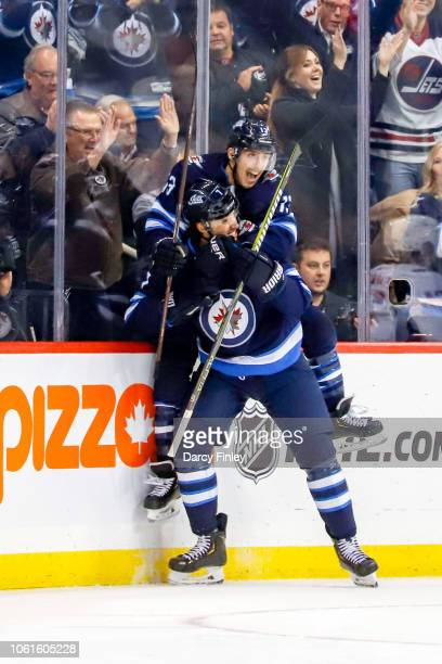 Brandon Tanev of the Winnipeg Jets jumps on the back of teammate Ben Chiarot as they celebrate a third period goal against the Washington Capitals at...