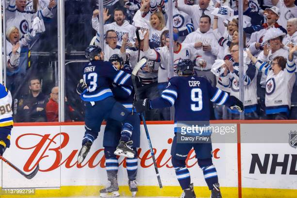 Brandon Tanev of the Winnipeg Jets leaps on teammate Adam Lowry as they celebrate a first period goal against the St Louis Blues in Game Five of the...