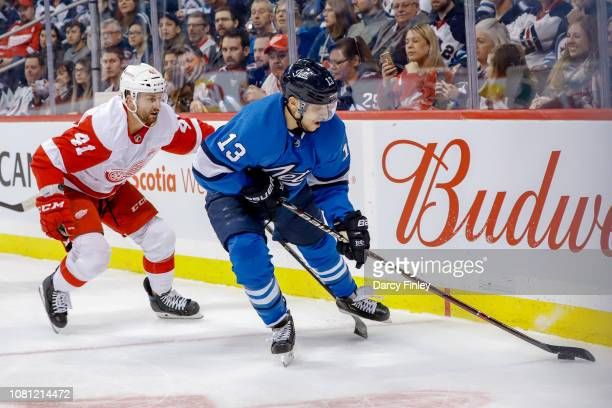 Brandon Tanev of the Winnipeg Jets plays the puck along the boards away from Luke Glendening of the Detroit Red Wings during first period action at...