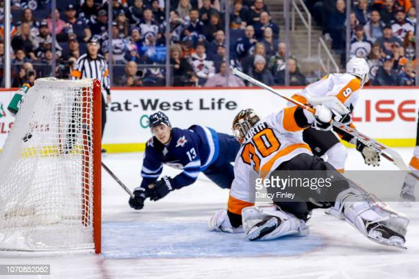 Brandon Tanev of the Winnipeg Jets watches as the puck gets in the net behind goaltender Michal Neuvirth of the Philadelphia Flyers for a second...