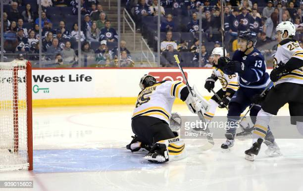 Brandon Tanev of the Winnipeg Jets watches as the puck goes into the net behind goaltender Anton Khudobin of the Boston Bruins for a second period...