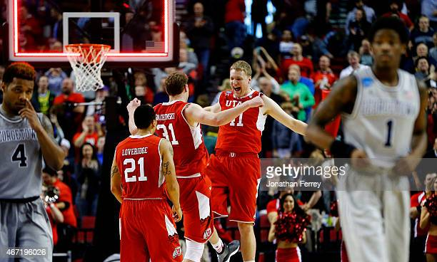 Brandon Taylor Dallin Bachynski and Jordan Loveridge of the Utah Utes celebrate their 75 to 64 win over the Georgetown Hoyas during the third round...